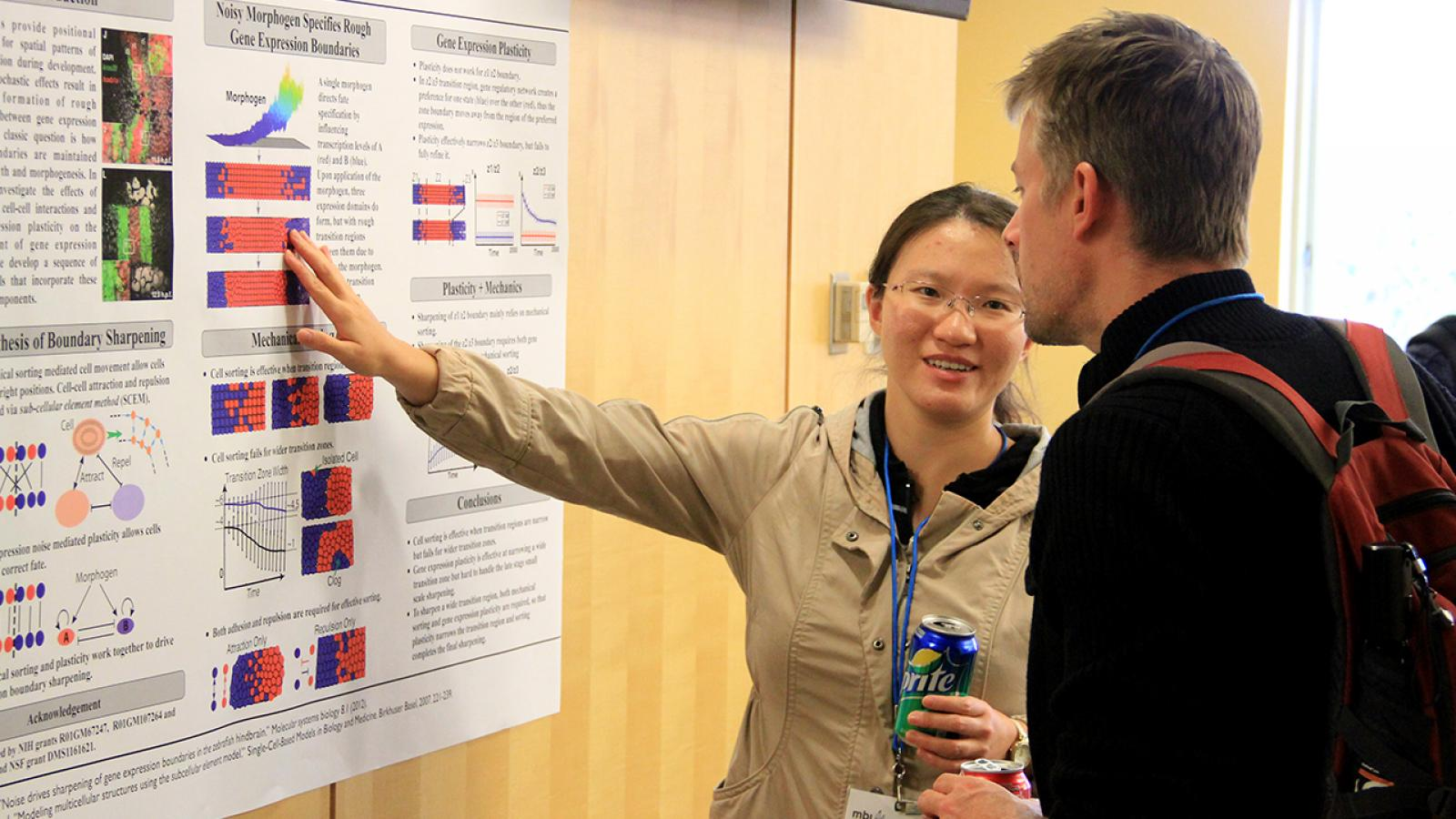 Photo of researcher explaining her poster
